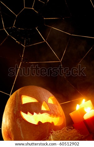 Image of Halloween pumpkin with burning candles and cobweb with spiders near by