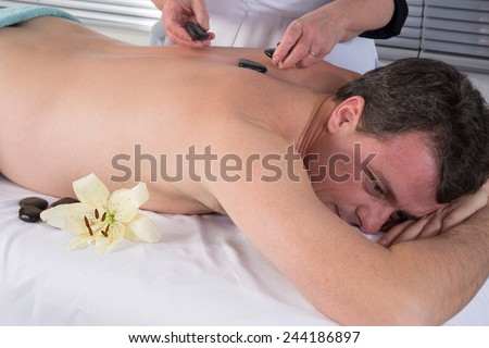 Image of hand placing Lastone on man\'s back in spa