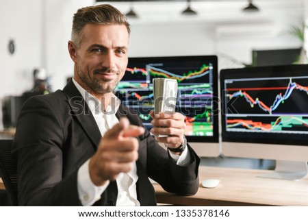 Image of handsome businessman 30s wearing suit holding pack of money while working in office with graphics and charts on computer