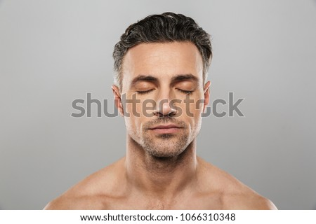 Image of handsome concentrated mature man standing isolated over grey wall background naked. Eyes closed.