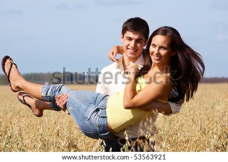 Image of handsome man holding beautiful girl while both looking at camera