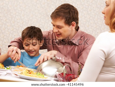 Image of handsome man showing how to cut roasted turkey to his son