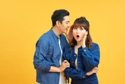 Image of handsome man whispering secret or interesting gossip to woman in her ear isolated over yellow background