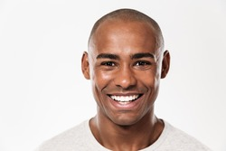 Image of handsome smiling young african man standing isolated over white background. Looking camera.