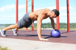 Image of handsome strong sports man doing exercises with fitness ball outdoors at sunny day