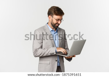 Image of handsome successful businessman working, standing in grey suit and using laptop, standing over white background Foto stock ©