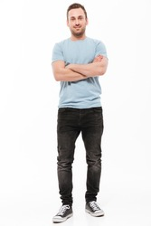 Image of handsome young cheerful man standing isolated over white background with arms crossed. Looking camera.
