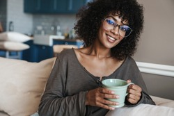 Image of happy african american woman in eyeglasses drinking coffee and smiling at home