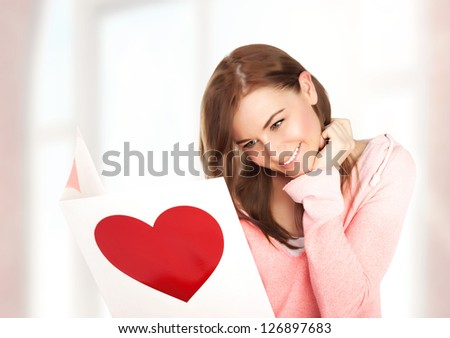 Image of happy beautiful female reading romantic postcard with big red heart, attractive brunette woman got sensual greeting card and isolated on white background, Valentine day,love concept
