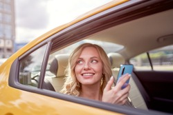 Image of happy blonde looking at side with phone in her hand sitting in back seat in yellow taxi