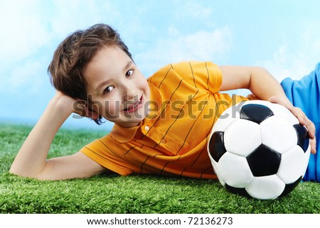 Image of happy boy lying on the grass with ball and looking at camera