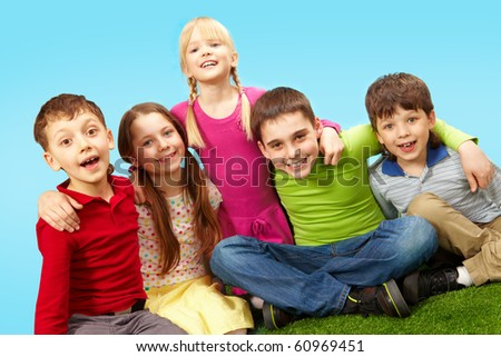 Image of happy boys and girls having rest on green grass