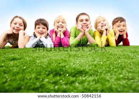 Image of happy boys and girls lying on a green grass - stock photo