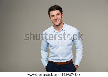 Image of happy brunette man wearing formal clothes smiling at camera with hands in pockets isolated over gray background