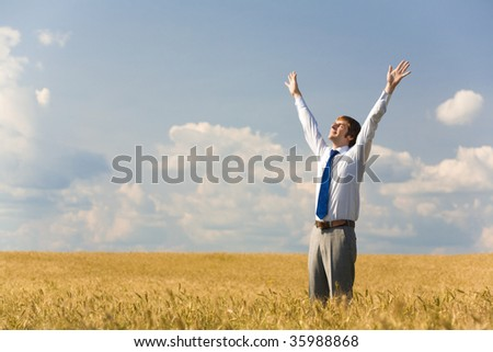 Image of happy businessman enjoying life and freedom in wheat field