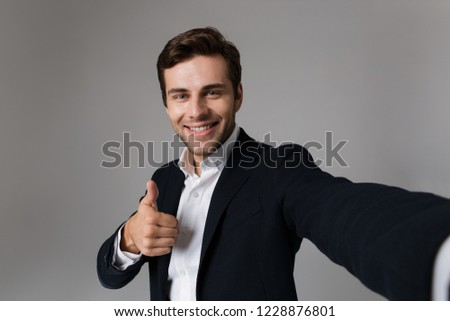 Image of happy businessman 30s in formal suit showing thumb up while taking selfie photo isolated over gray background