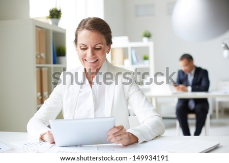 Image of happy businesswoman sitting at workplace and using touchpad