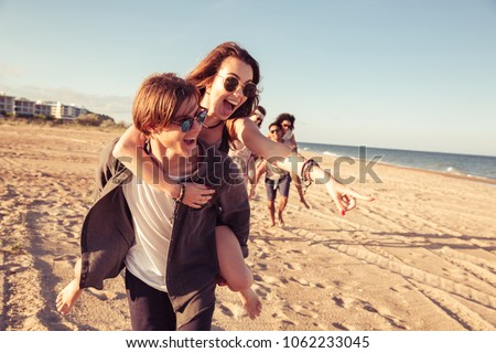 Image of happy cheerful young loving couples friends walking outdoors on the beach having fun.