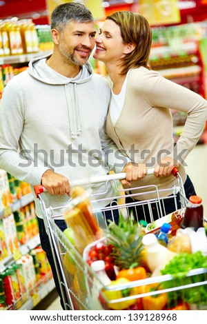 Image of happy couple with cart flirting in supermarket