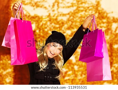 Image of happy cute girl with pink shopping bag, cheerful young lady holding paper presents bags in fall park, smiling blond woman raised up hands over golden autumn background, spending money concept