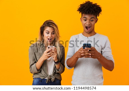 Image of happy cute young loving couple posing isolated over yellow background using mobile phones. #1194498574