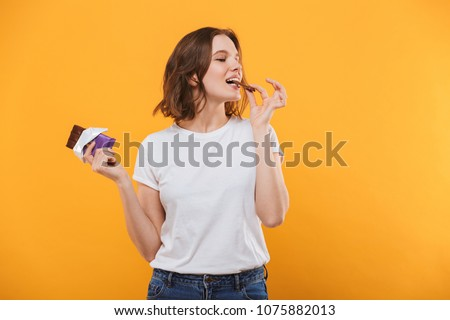 Image of happy cute young woman standing isolated over yellow background eating chocolate.
