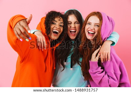 Image of happy emotional young three multiethnic girls friends posing isolated over pink wall background. Foto d'archivio ©