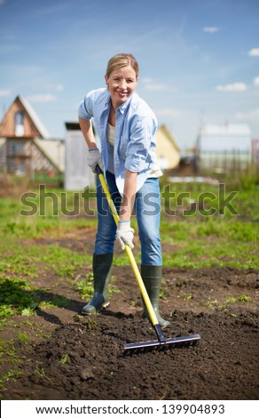 Image of happy female farmer working in the garden
