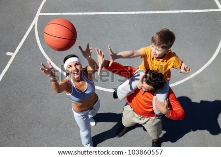 Image of happy female throwing ball with man and kid near by