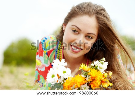 Image of happy female with wildflowers on summer day - stock photo
