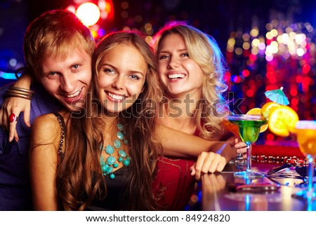 Image of happy friends looking at camera at party
