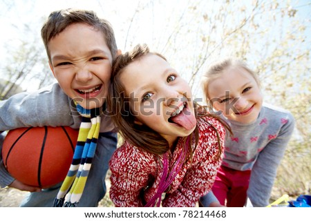 Image of happy friends looking at camera with funny girl showing her tongue in front