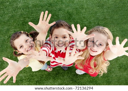 Image of happy friends on the grass raising arms