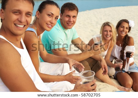 Image of happy friends with drinks having fun at beach party