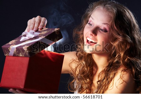 Image of happy girl looking into gift box and wondering #56618701