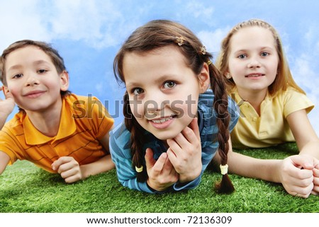Image of happy girl lying on the grass and looking at camera with friends at background