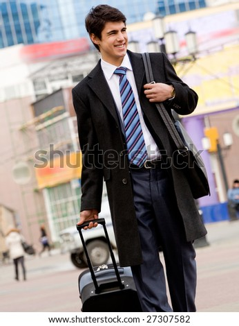 Image of happy guy in suit and coat walking with his baggage and bag