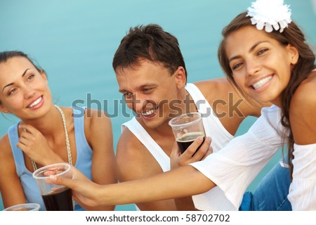 Image of happy guy with drink surrounded by girls at beach party