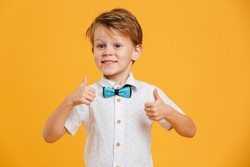 Image of happy little boy child standing isolated over yellow background. Looking camera showing thumbs up.