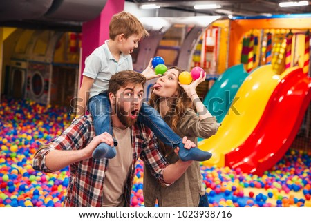 Image of happy little child have fun with his parents in entertainment game center.