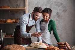 Image of happy loving couple bakers standing near bread and looking at mobile phone.