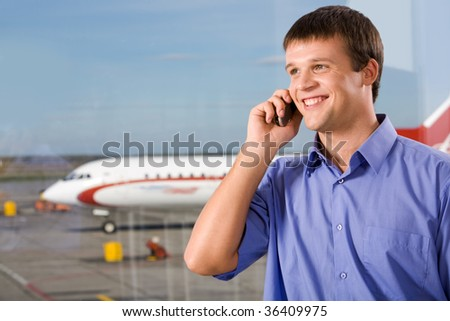 Image of happy male speaking by the mobile phone in airport