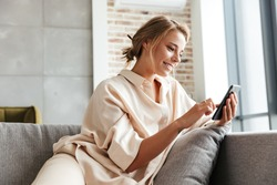 Image of happy nice woman in pajamas smiling and using cellphone while sitting on sofa at living room