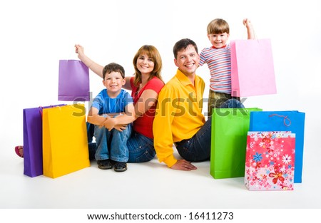 Image of happy parents and their two sons sitting in studio with shopping bags near by