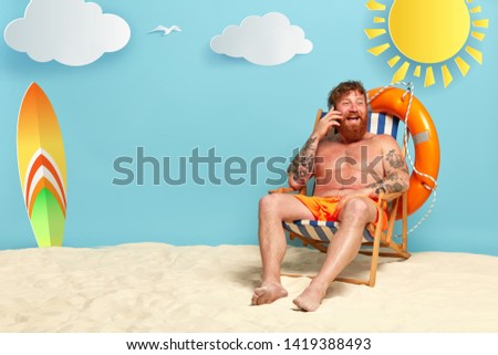 Image of happy redhead man in shorts glad to have telephone conversation with friend, has red sunburnt skin, tells about vacation at resort place, laughs positively, expresses good emotions. #1419388493