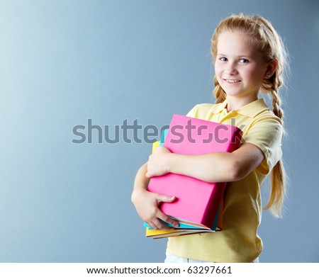 Image of happy schoolgirl with books looking at camera