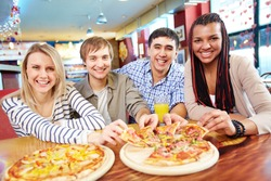 Image of happy teenage friends eating pizza in cafe