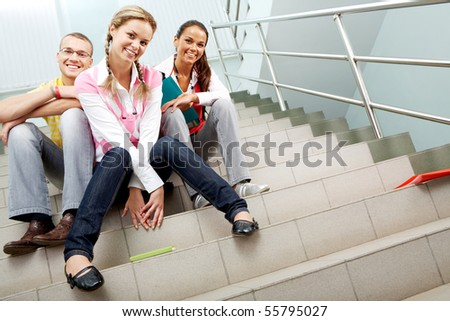 Image of happy teenagers sitting in the corridor of college and looking at camera
