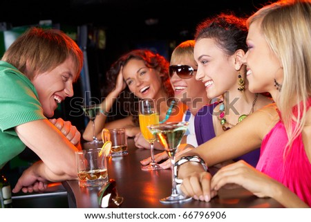 Image of happy teenagers with cocktails chatting and having fun in the bar