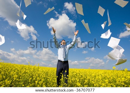 Image of happy winner throwing papers in yellow meadow - stock photo